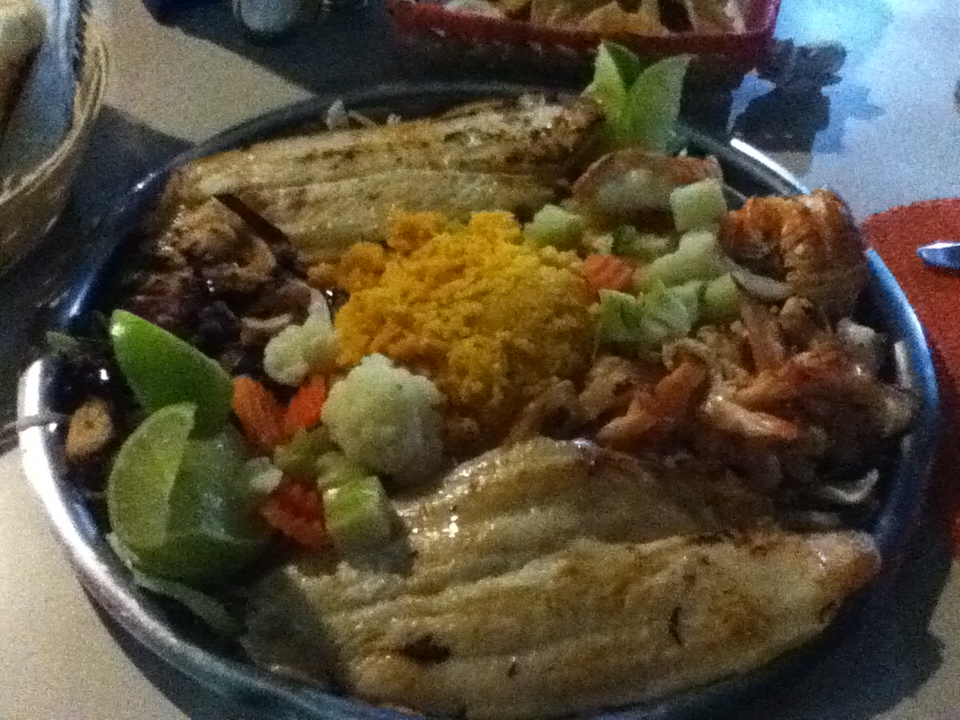 A plate full of fish, rice, and other foods.