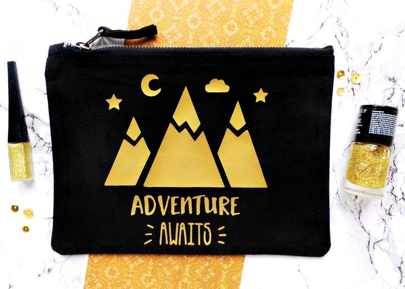 adventure awaits make up bag with 3 mountains in gold