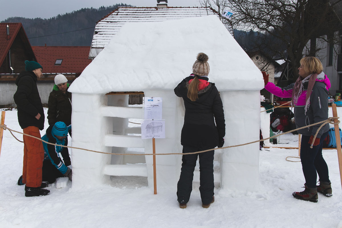 people building a snow kozolec (hayrack)