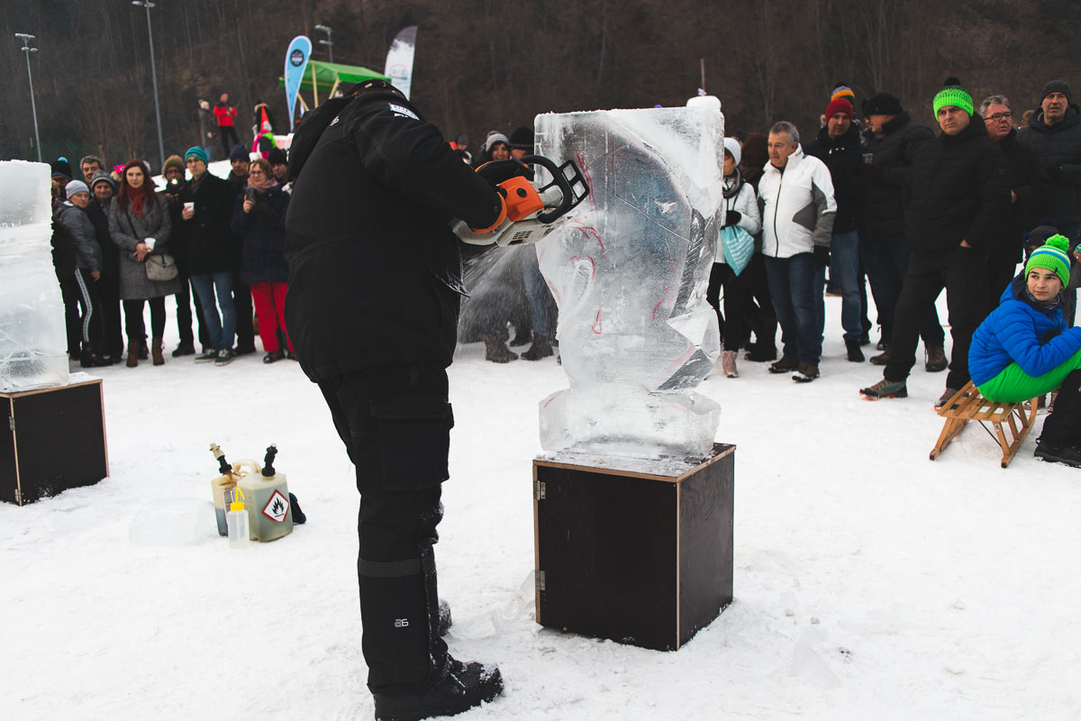 man carving ice sculpture with chainsaw